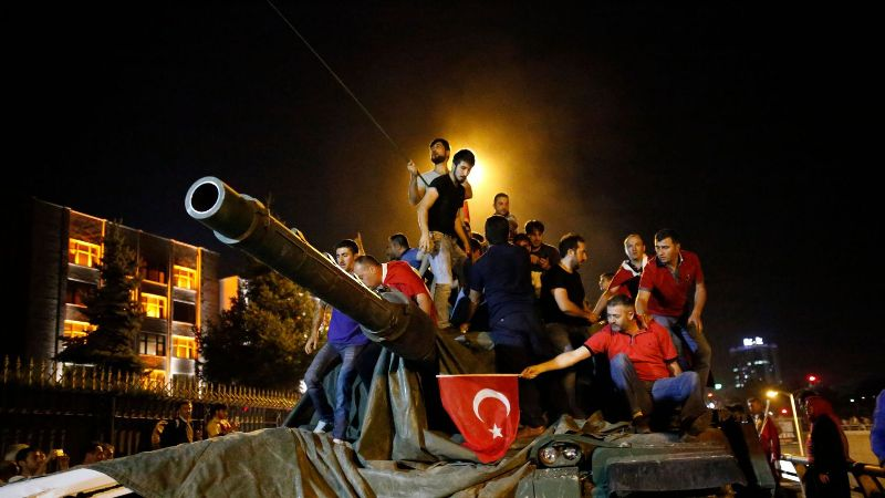 people stand on a turkish army tank in ankara